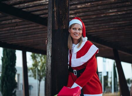 Stock photo of mama noel leaned on a wooden pole with expression of happiness. Christmas time