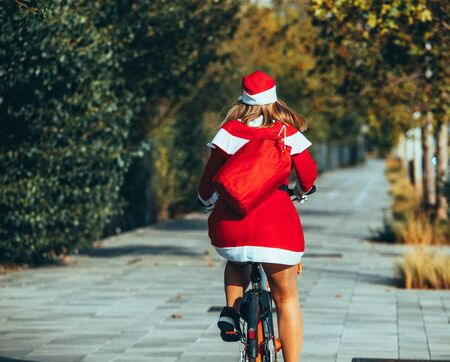 Stock photo of Mama noel with her back to the street riding a bicycle. Christmas time