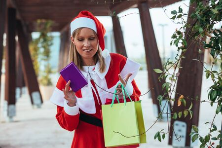 Stock photo of mama noel showing a gift with one hand and gift bags in the other hand. Christmas time