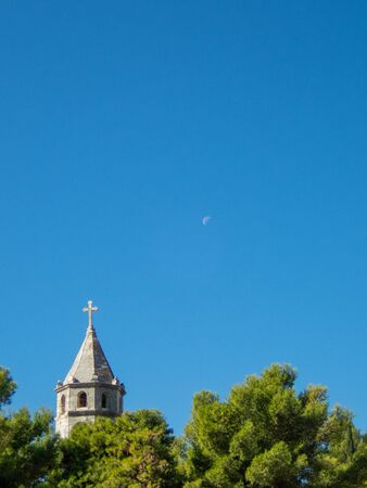 Stock vertical photo of Tower of a catholic church with a tree in Cavtat, Croatia. Travel concept Reklamní fotografie