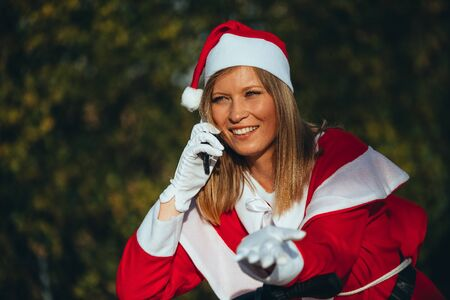 Stock photo of Mama noel talking at the mobile resting on the handlebars of the bicycle with expression of happiness. Christmas time Reklamní fotografie