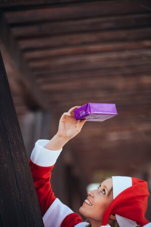 Vertical stock photo of Mama noel looking at a gift she holds with her hand in the air. Christmas time