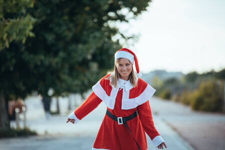 Stock photo of Mama Noel walking to a tree-lined promenade in the street. Christmas time