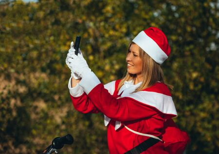 Stock photo of Mama noel making herself a selfie on the bicycle with expression of happiness