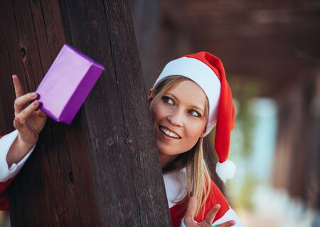 Stock photo of mama noel pointing with a gift in her hand and leaned on a wooden pole. Christmas time