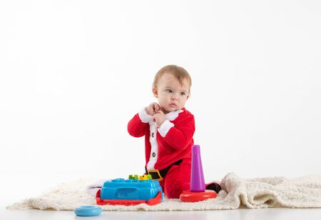 Stock studio photo with white background with a baby dressed as Santa Claus sitting on the floor playing with plastic toys.