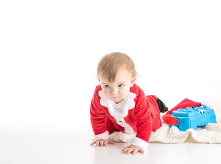 Stock studio photo with white background of a baby dressed like Santa crawling. Portrait