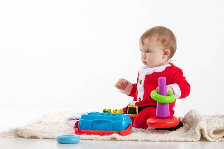 Stock studio photo with white background with a baby dressed as Santa Claus sitting on the floor playing with toys.
