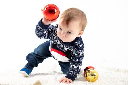 Stock studio photo with white background with a baby playing with Christmas balls. Portrait and family