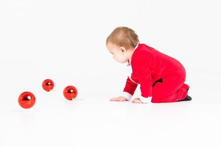 Stock studio photo with white background with a baby dressed as Santa playing with Christmas balls Reklamní fotografie
