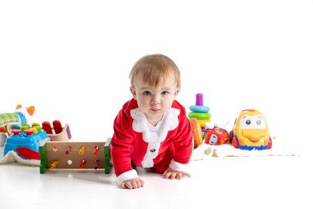 Foto de estudio de stock con fondo blanco de un bebé vestido como Santa arrastrándose en medio de juguetes de plástico. Retrato Foto de archivo