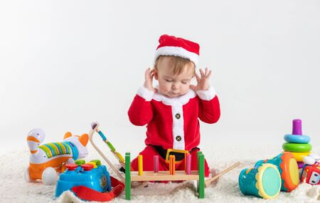 Stock studio photo with white background with a baby dressed as Santa Claus sitting on a blanket playing with wooden and plastic toys. Stock Photo