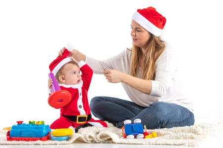 Stock studio photo with a white background of a mother and child dressed for Saint Claus sitting playing on the floor.