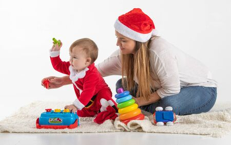 Stock studio photo with a white background of a mother and child dressed for Saint Claus sitting playing on the floor. Banque d'images - 135432586