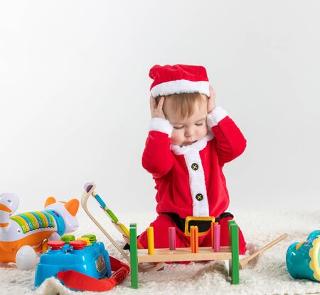 Stock studio photo with white background with a baby dressed as Santa Claus sitting on the floor playing with wooden and plastic toys.