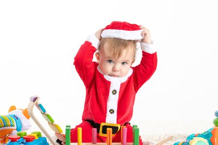 Stock studio photo with white background with a baby dressed as Santa Claus sitting on a blanket, playing with wooden and plastic toys and touching his hat Banque d'images - 135432460