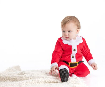Stock studio photo with white background with a baby dressed as Santa Claus sitting on the floor