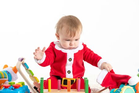 Stock studio photo with white background with a baby dressed as Santa Claus sitting on a blanket, playing with wooden and plastic toys and touching his hat Stock Photo