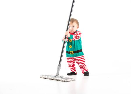 Stock studio photo with a white background of a baby disguised as an elf clinging to the stick of a mop