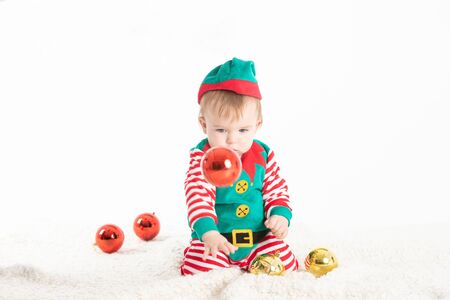 Stock studio photo with white background of a baby disguised elf with hat removed from head rolled from Christmas balls Reklamní fotografie