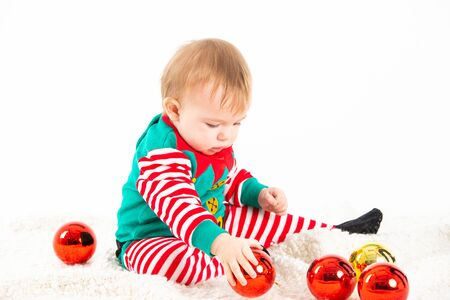 Stock studio photo with white background of a baby in elf costume playing with christmas balls