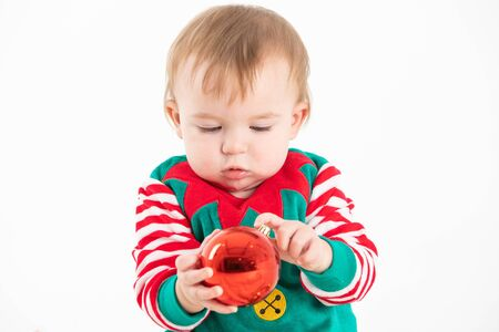 Stock studio photo with white background of a baby in elf costume grabbing a christmas balls
