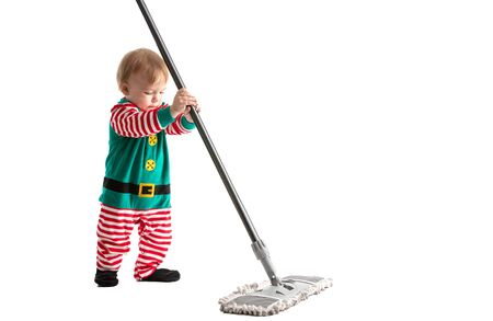 Stock photo of a studio with white background of a baby disguised as a goblin playing with the stick of a mop.