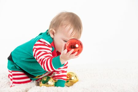Stock studio photo with white background of a baby in elf costume grabbing christmas balls