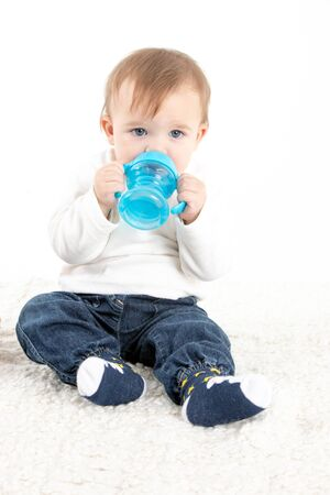 Stock studio photo with a white background of a baby drinking water from a canteen with handles.