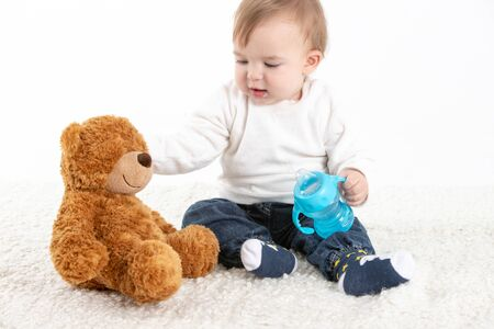 Stock studio photo with a white background of a baby sitting with a canteen with handles and a teddy bear.