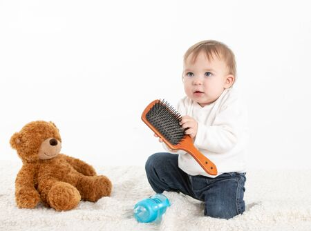 Stock studio photo with a white background of a baby playing with a comb