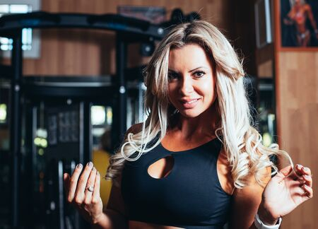 Stock photo of a Portrait of a fitness blonde girl with a black top in the gym. Fitness and leisure