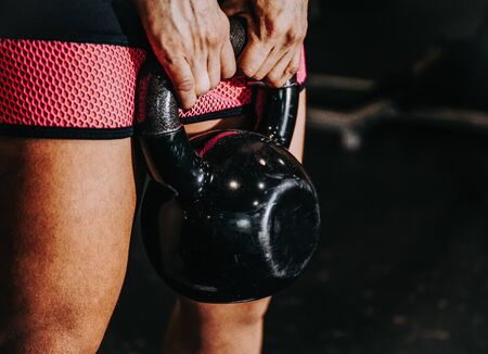 Stock photo of a detail of hands holding a kettlebell in the gym