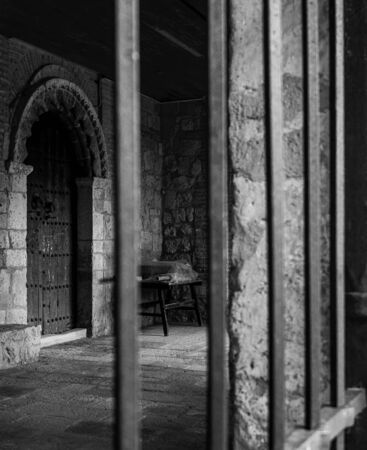 Black and white vertical photo of the door of a medieval stone building with columns and iron bars in Maderuelo in Spain