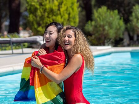 Stock photo of Two girls of different ethnicities in the water of a swimming pool embraced while one of them carries an lgtb flag that covers her. Lifestyle