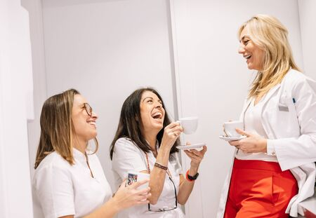 Happy young women in medical uniform enjoying hot drink and laughing while communicating during break in modern clinic