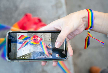 Top view of crop anonymous female in rainbow bracelet taking photo of LGBT flags while using smartphone on street