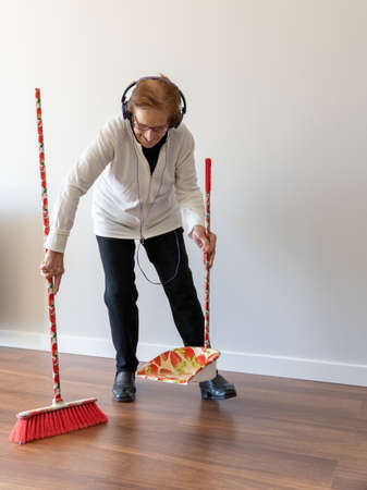 Cheerful 90 year old female enjoying music in headphones while sweeping floor with broom and doing housework