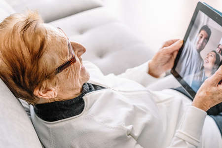 High angle side view of satisfied senior female resting on sofa at home and having video call with family while using tablet