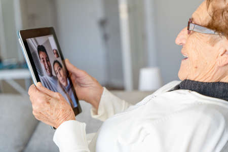 High angle side view of satisfied senior female resting on sofa at home and having video call with family while using table Foto de archivo