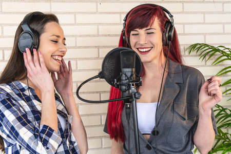 Happy young women with headset standing near microphone and enjoying singing against brick wall and plant