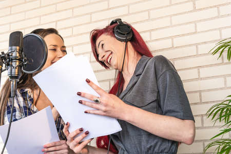 Low angle of happy voice actresses with scripts laughing at joke and looking at each other while preparing to dub film in studio