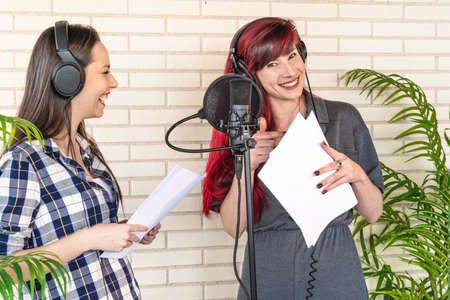 Happy young women with scripts smiling and resting near microphone during break in film dubbing session