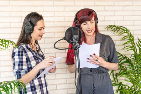 Young women in headphones reading script from papers while standing near microphone and dubbing movie in studio Foto de archivo