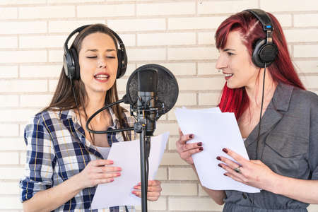 Happy young voice actresses in headphones smiling and reading script near microphone while creating soundtrack for movie against brick wall
