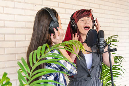Young female vocalists singing with closed eyes near microphone during performance near green plants