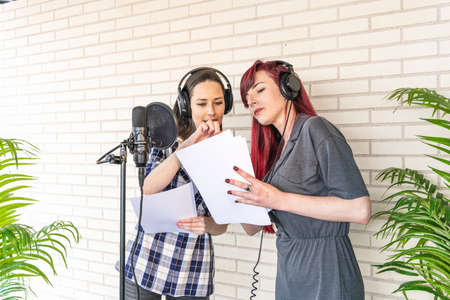 Young women in headphones discussing script while standing near microphone against brick wall in film dubbing studio Foto de archivo