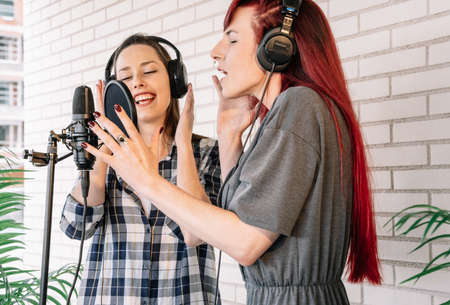 Young women with closed eyes gesticulating and singing into microphone while listening to music in headphones in light professional studio Foto de archivo