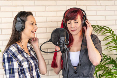 Happy young female in headphones smiling and listening to girlfriend singing song with closed eyes while recording music against brick wall in studio