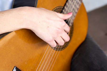 From above anonymous woman with manicure playing acoustic guitar during music session in studio